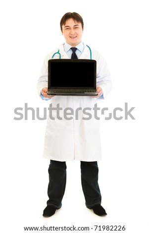 Smiling  doctor holding laptop with blank screen in hands  isolated on white