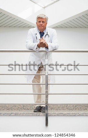 Smiling doctor leaning on rail in hospital corridor