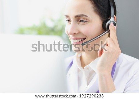 Smiling doctor operator at workplace is providing medical assistance remotely. First aid concept