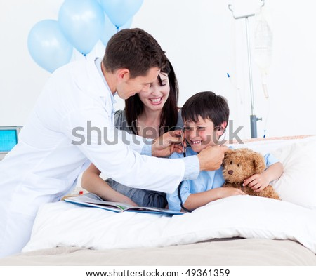 Smiling doctor playing with a little boy and his mother at the hospital