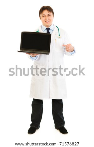 Smiling  doctor pointing finger on  laptop with blank screen  isolated on white