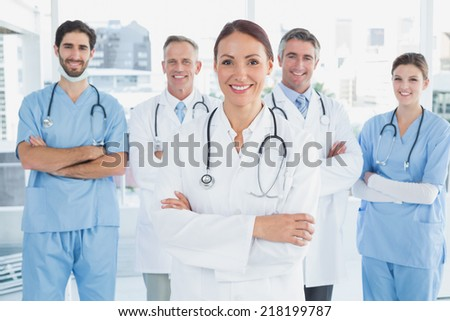 Smiling doctor with fellow doctors standing behind her