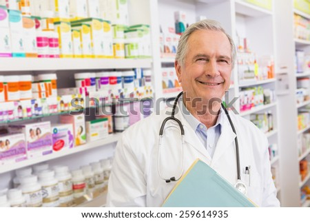 Smiling doctor with stethoscope holding notebooks in the pharmacy