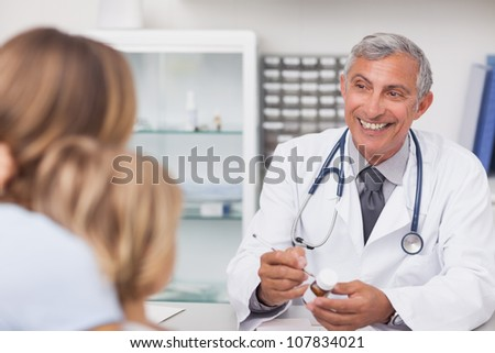 Smiling doctor writing on a drug box in a medical office