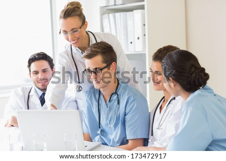 Smiling doctors and nurses discussing over laptop in hospital