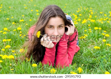 smiling dreaming girl lying among dandelions