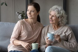 Smiling dreamy mature mother with grownup daughter drinking tea or coffee, holding cups, sitting on couch in living room, elderly woman with granddaughter looking to aside, dreaming about good future