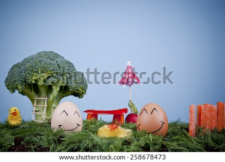 Smiling eggs in a garden made of vegetables: broccoli tree, red pepper bench, carrot fence and dill grass, concept.