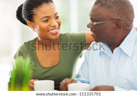 smiling elderly african american man enjoying coffee with his granddaughter at home
