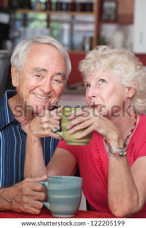 Smiling elderly couple with mugs at a coffeehouse