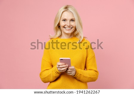 Smiling elderly gray-haired blonde woman lady 40s 50s years old in yellow casual sweater standing using mobile cell phone typing sms message isolated on pastel pink color background studio portrait