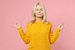 Smiling elderly gray-haired blonde woman lady 40s 50s years old in yellow sweater hold hands in yoga gesture relaxing meditating, trying to calm down isolated on pink color background studio portrait