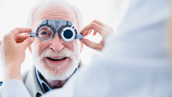 Smiling elderly man checking up vision with special ophthalmic glasses