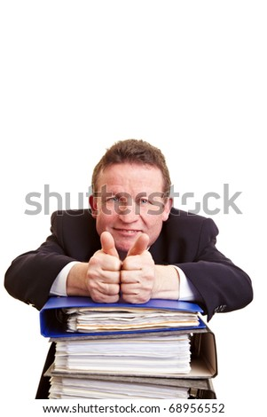Smiling elderly manager with files holding his thumbs up
