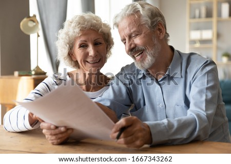 Smiling elderly 50s husband and wife sit at table in living room read contract agreement satisfied with terms and rules, happy old 60s couple customers or clients glad with pension health insurance Stock foto ©