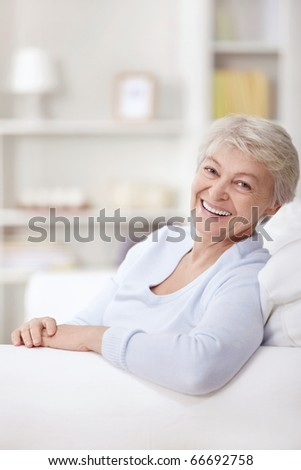 Smiling elderly woman at home on the couch