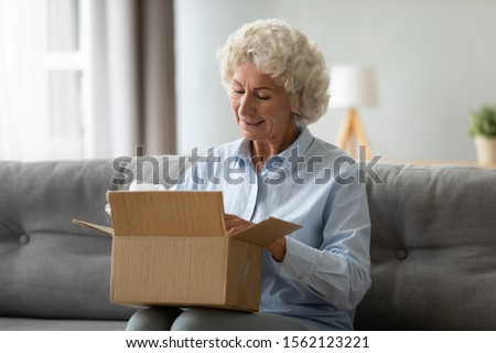Smiling elderly woman customer receive post shipment parcel at home, happy old senior grandma hold open cardboard box sit on sofa in living room, online shopping order fast courier delivery concept
