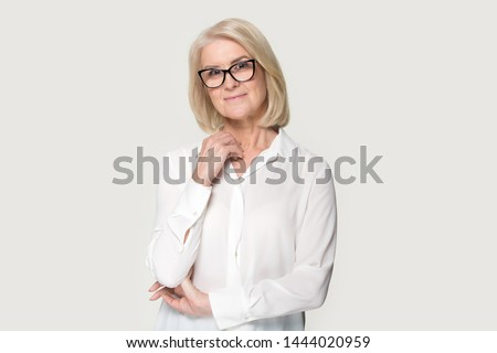 Smiling elderly woman in glasses feeling shy posing at studio. Beautiful old lady looking at camera feeling uncertain, unsure, anxious. Studio headshot isolated on grey background. People emotions