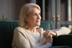 Smiling elderly woman look in distance feel cheerful positive remembering good old days, happy mature female sit on couch at home thinking, enjoying pleasant memories, recollecting or visualizing