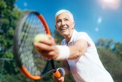 Smiling Elderly Woman Playing Tennis as a Recreational Activity