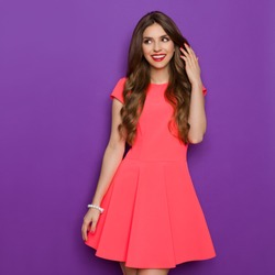 Smiling elegance young woman in pink mini dress holding hand in hair and looking away. Three quarter length studio shot on purple background.