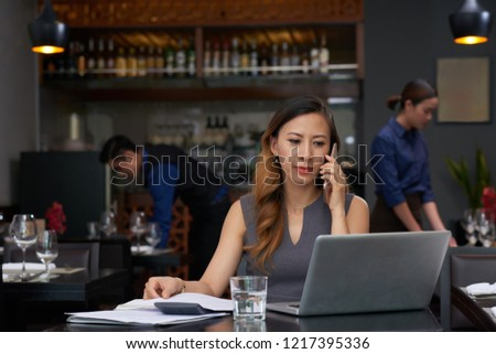 Smiling elegant business lady talking on phone and reading e-mails on laptop screen Stock foto ©