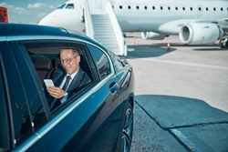 Smiling elegant man in glasses is using cell phone during transfer after trip by plane