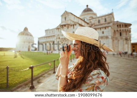 smiling elegant middle aged traveller woman in floral dress with film camera and hat near Pisa Cathedral. Stock photo ©