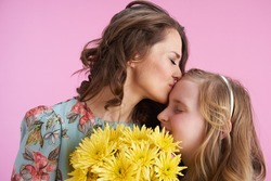 smiling elegant mother and daughter with long wavy hair with yellow chrysanthemums flowers hugging and kissing against pink background.
