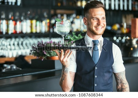 Smiling elegant waiter is holding a tray with a decorated cocktail ready to serve