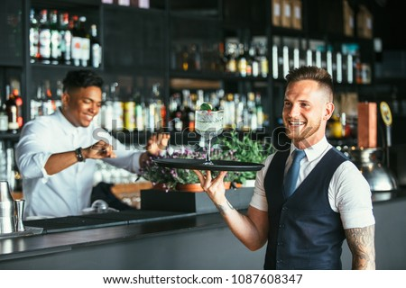 Smiling elegant waiter is holding a tray with a decorated cocktail with a smiling mixed race male expert bartender at the bar counter at the background