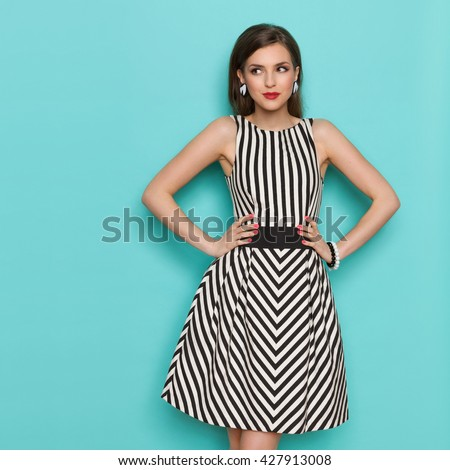Smiling elegant woman in black and white striped dress posing with hands on hip and looking away, Three quarter length studio shot on turquoise background.