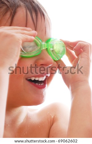 smiling elementary age boy  with wet hair and goggles laughing