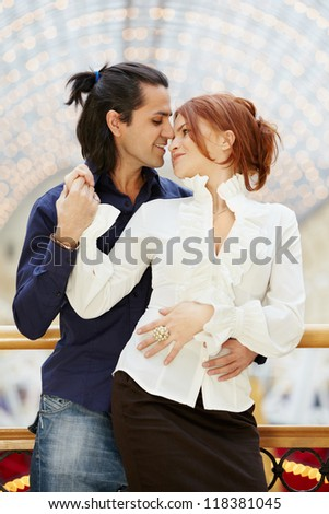Smiling embracing young couple stands leaned on banister