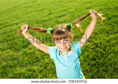 Smiling emotional Little girl in park holding her hair - stock photo