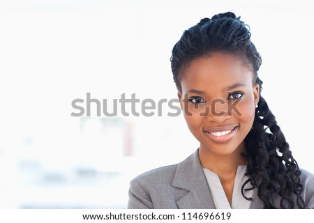 Smiling employee standing upright in front of a window while wearing a formal suit