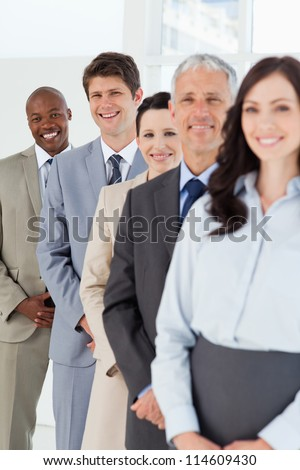 Smiling employees standing in the back while laughing and following their team - stock photo