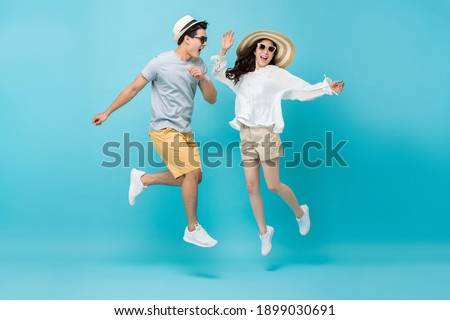 Smiling energetic Asian couple tourists in summer beach casual clothes jumping isolated on light blue studio background