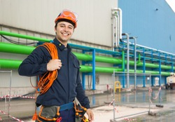 Smiling engineer at work in front of a factory