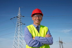 Smiling Engineer in Red Hardhat and Yellow West Standing Under The Electrical Transmission Towers. Happy Manager in Red Hardhat, Blue Shirt and Yellow Vest Looking at Camera.