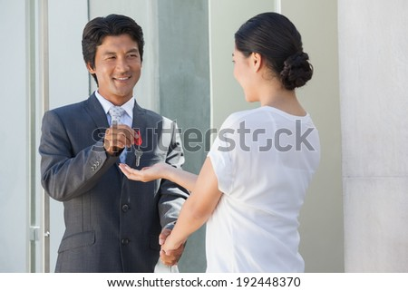 Smiling estate agent giving the key to buyer outside new home #192448370