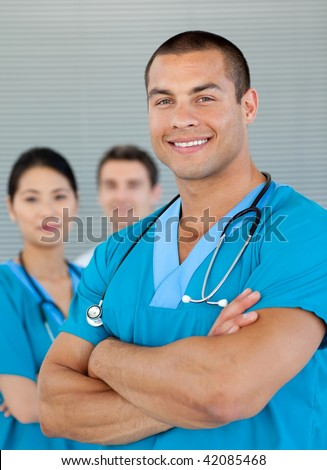 Smiling ethnic doctor with his colleagues in the background. Medical concept.