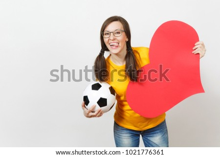 Smiling European woman, fun pony tails, football fan or player in glasses, yellow uniform hold classic soccer ball, red heart isolated on white background. Sport, football, healthy lifestyle concept