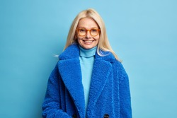 Smiling European woman with blonde hair dressed in blue winter coat has happy mood wears eyewear poses in studio. Fashionable middle aged blonde lady in outerwear going to have walk with family
