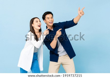 Smiling excited Asian couple pointing hands upward to empty space on isolated light blue background