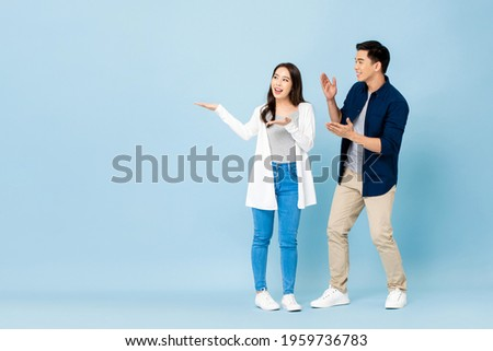 Smiling excited Asian couple tourists pointing hands to empty space aside on isolated light blue background