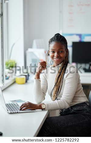 smiling excited hardworking african employee dressed casually looking at the camera. beauty,