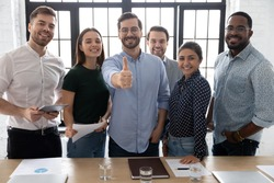 Smiling executive showing thumb up, standing with diverse employees team in modern office room, looking at camera, smiling businessman recommending corporate service, good career, human resources