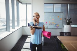 Smiling executive talking on mobile phone while holding exercise mat and shoes in office