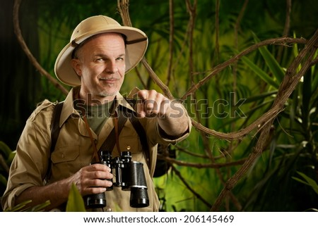 Smiling explorer in the jungle with binoculars pointing at camera. #206145469